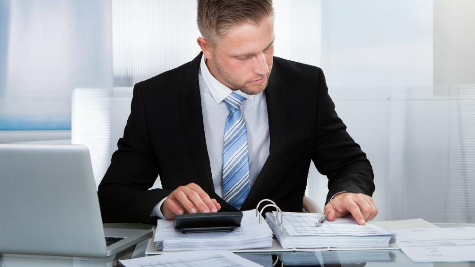 Homem executivo usa calculadora para conferir dados do caderno