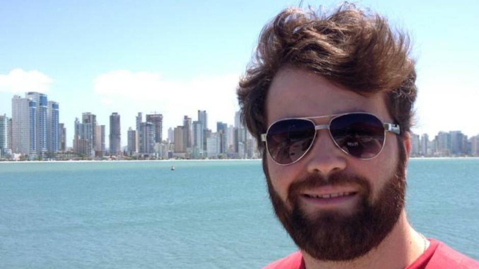 Jovem de oculos escuros sorrindo com cidade ao fundo