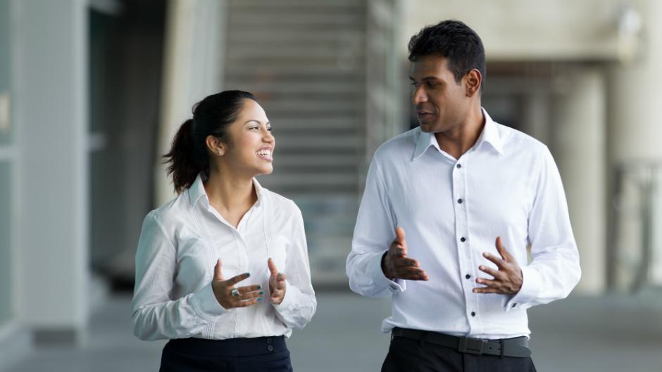 Mulher conversando com homem em trajes formais