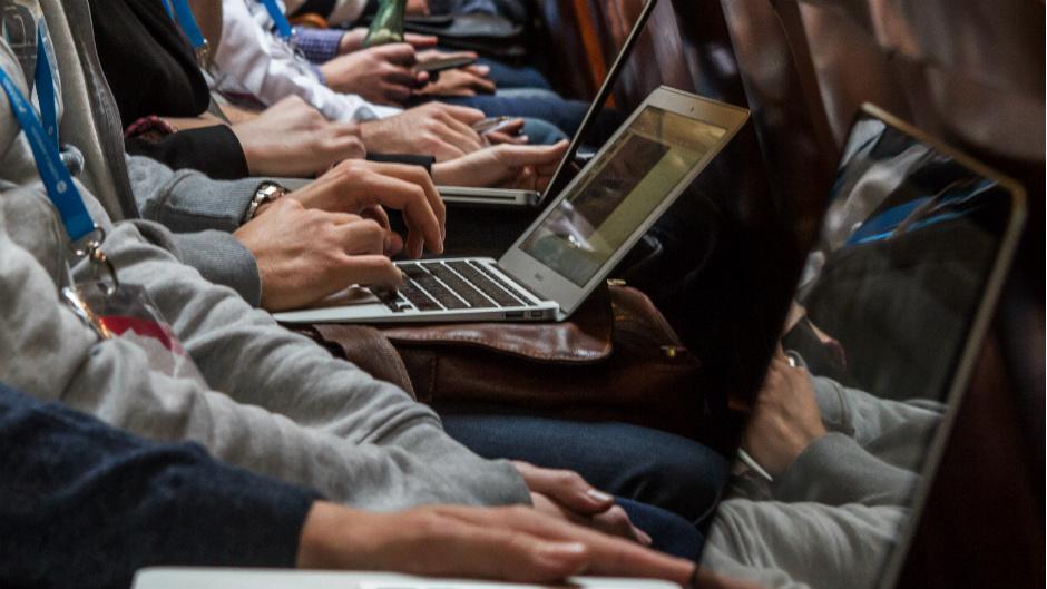 Pessoas com laptops no colo em sala