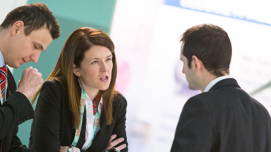 Jovem executiva discute com homens de terno