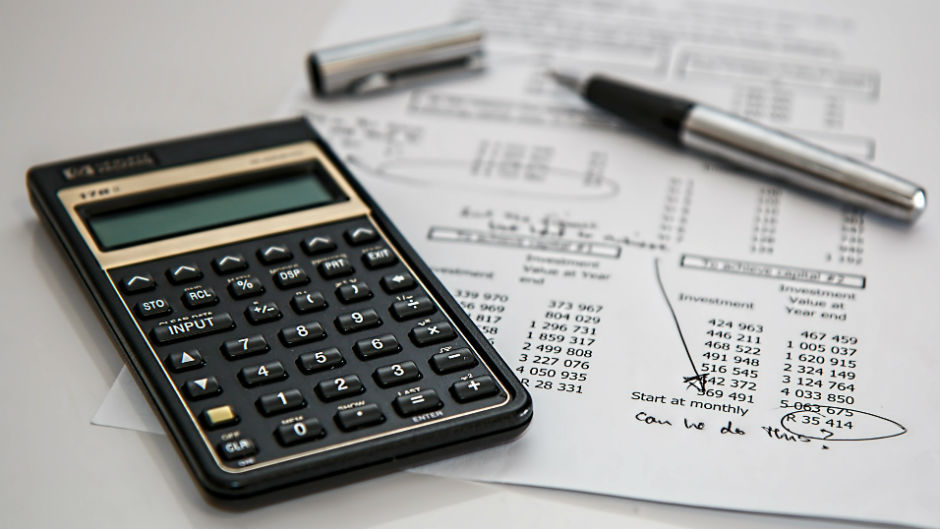 Calculadora e caneta sobre papel