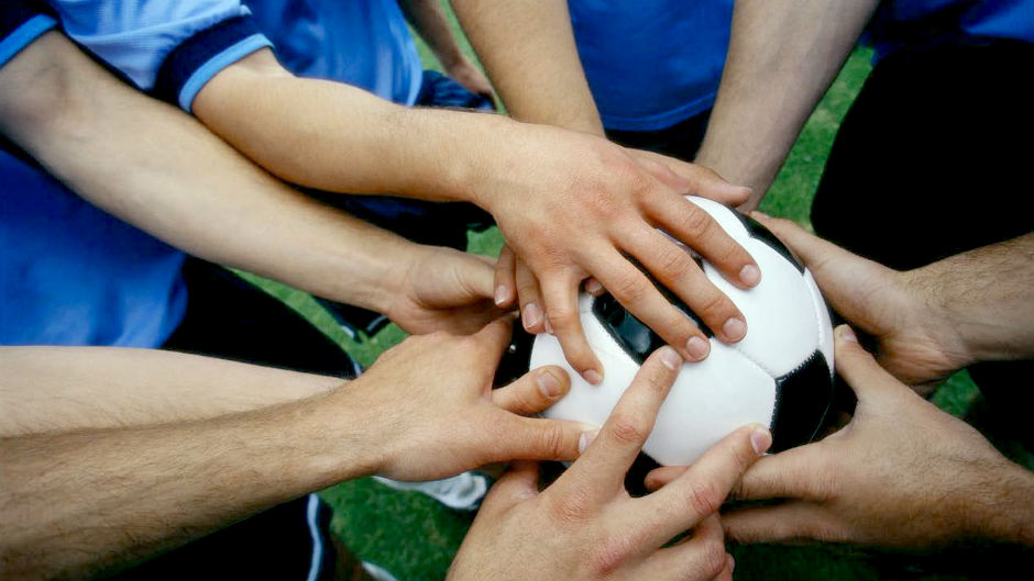 Time de futebol põe as mãos na bola antes do jogo