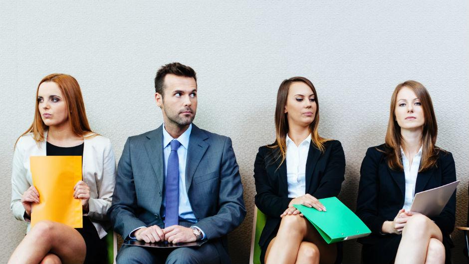 jovens aguardam sentados com curriculo na mao