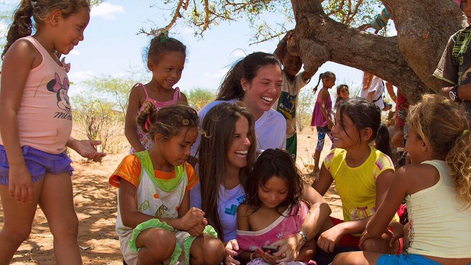 Mulher sorrindo abraçando crianças