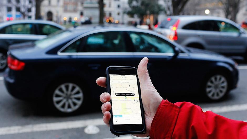 Pessoa segurando celular com aplicativo do uber