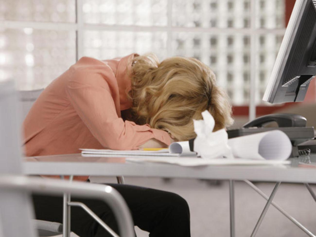 Mulher dormindo na mesa do escritório