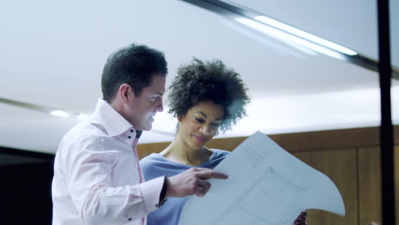 Homem e mulher lendo papel em ambiente de trabalho - Como escolher seu programa de trainee?