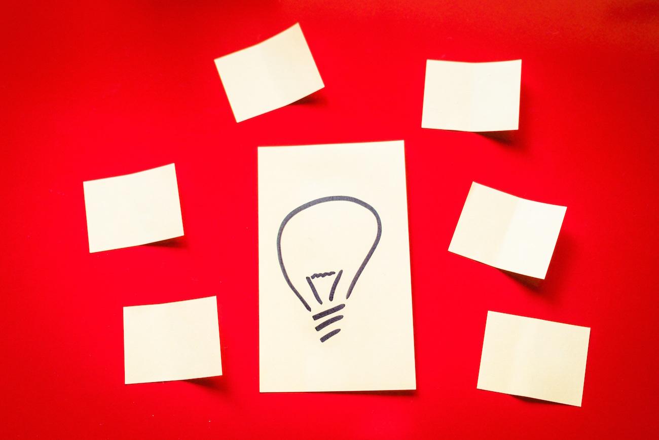 Desenho de uma lâmpada cercado por papeis em brancos sobre mesa vermelha - Descubra tipos de empreendedores