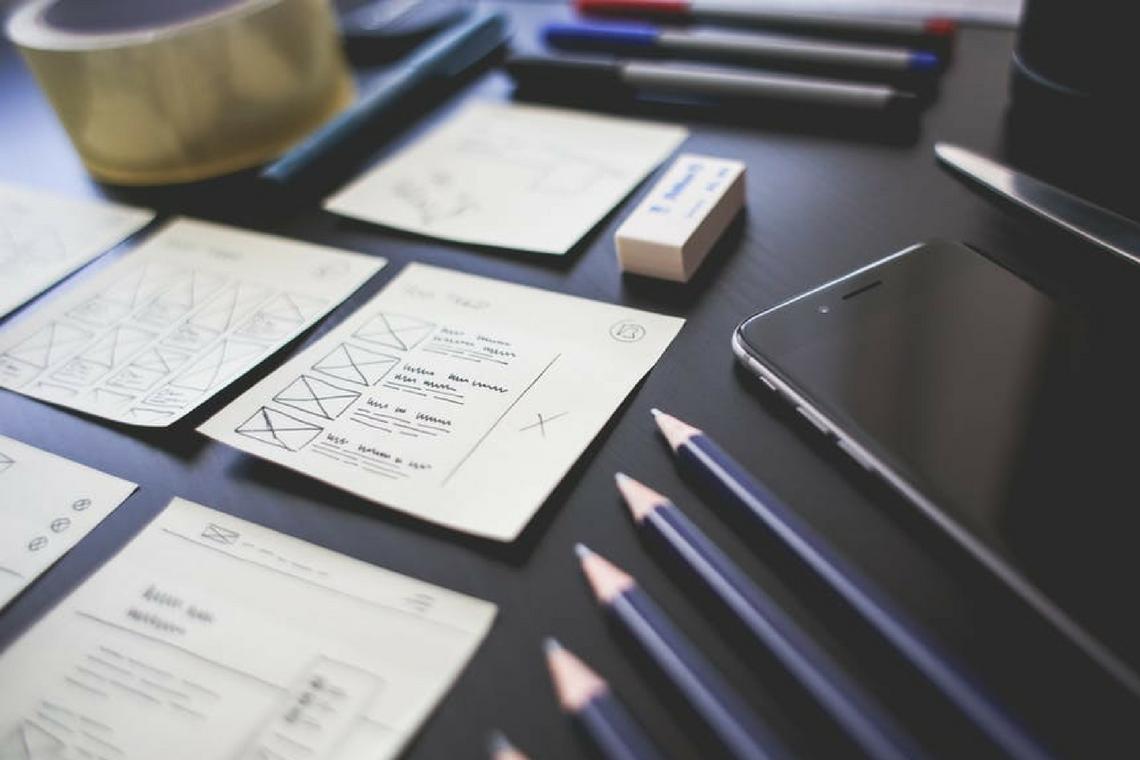 Papeis, lápis, borracha e celular em cima de uma mesa para representar prototipagem