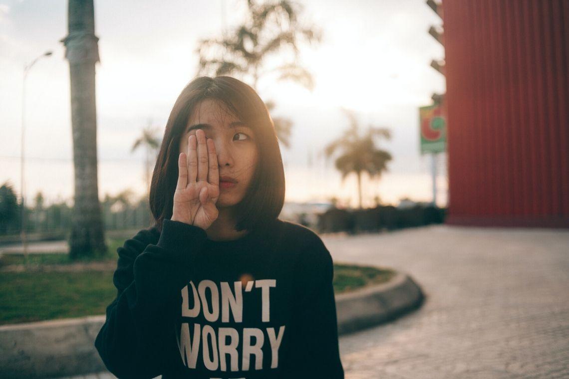 mulher tampa olho com quatro dedos