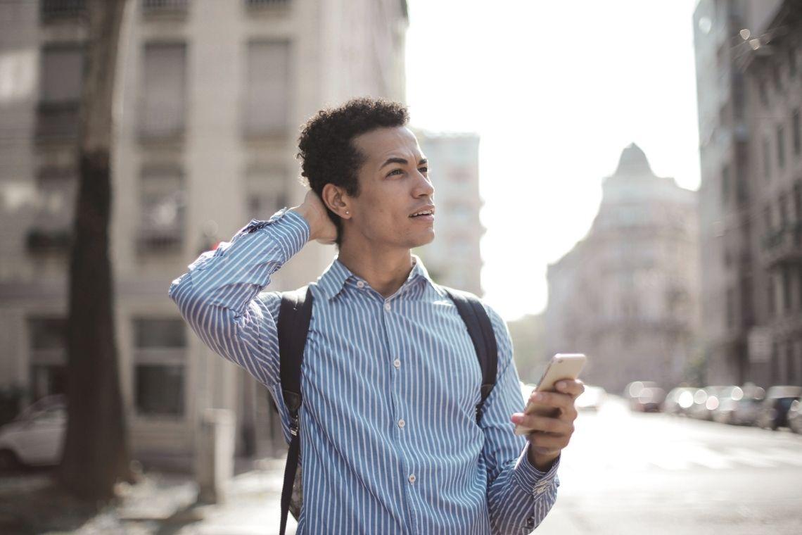 jovem preocupado com celular na mão e mochila nas costas